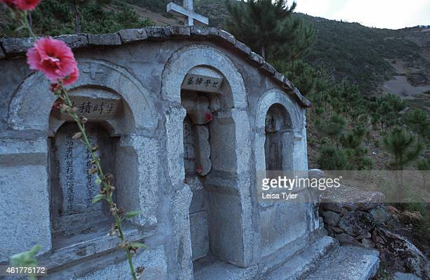 The grave of a Catholic worshipper overlooks the Mekong River valley above Cizhong in Northern Yunnan Brought to the area by French missionaries in...