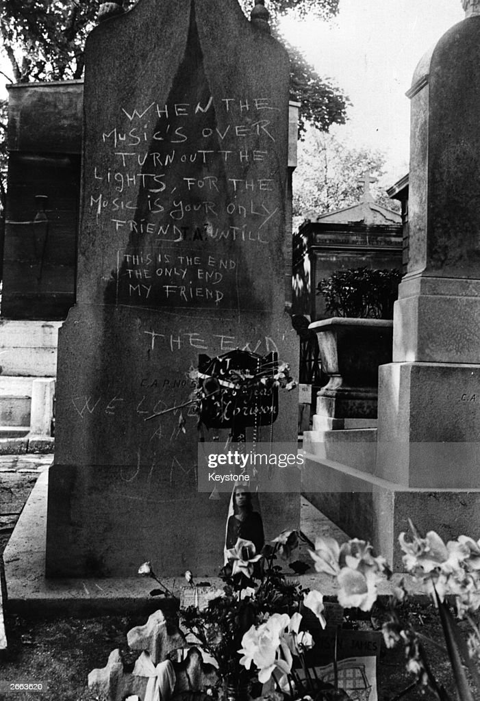 The grave of Jim Morrison (1943 - 1971), lead singer of The Doors, strewn with flowers, with a fan's tribute on a nearby headstone at the Pere Lachaise cemetery, Paris. Original Publication: People Disc - HC0071