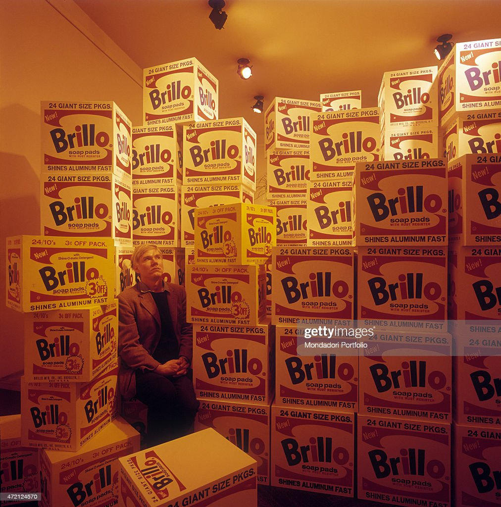 'The great American artist Andy Warhol, the guru of Pop Art movement, poses seated and surrounded by stacks of Brillo boxes, a firm producing detergents. 1964. (Photo by Mario De Biasi\Mondadori Portfolio via Getty Images)'