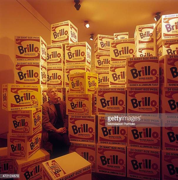 The great American artist Andy Warhol the guru of Pop Art movement poses seated and surrounded by stacks of Brillo boxes a firm producing detergents...