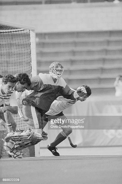 The Great Britain goalkeeper Ian Taylor and other team players race to intercept a penalty shot during the pool B game between Pakistan and Great...