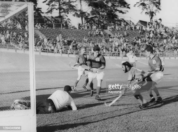 The Great Britain goalkeeper protects his goal from Indian hockey player Balbir Singh Sr in the semifinal of the men's field hockey tournament at...