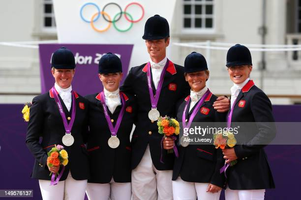 The Great Britain team celebrate on the podium after being presented with the Silver medal in the Eventing Team Jumping Final Equestrian event on Day...