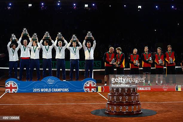 The Great Britain team pose with their trophies following victory as the defeated Belgium team look on on day three of the Davis Cup Final 2015 at...