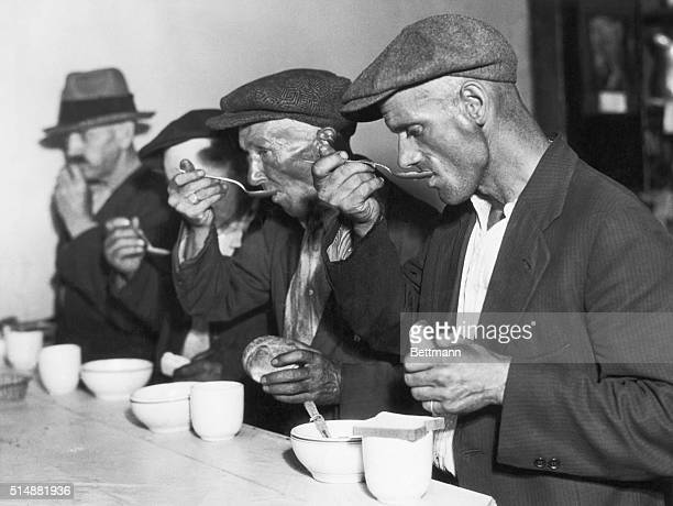 The Great Depression in the U.S.: Men eating bread and soup in a breadline. Undated photograph.BPA2# 1048