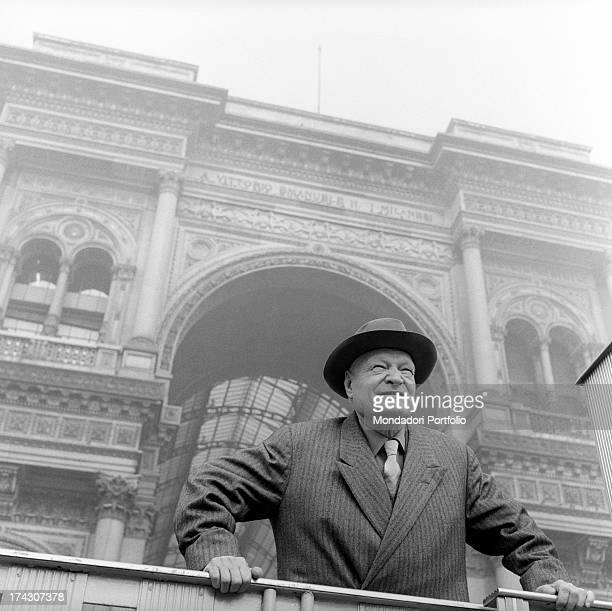 The great Italian poet Giuseppe Ungaretti, leaning on a railing, stands in front of the entrance arch of the Galleria Vittorio Emanuele II, looking...