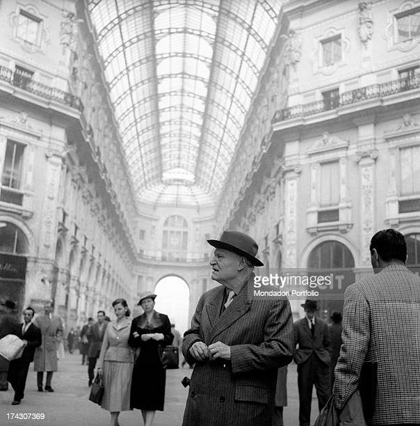 The great Italian poet Giuseppe Ungaretti looks around in the octagonal hall full of shopping people, in the center of the Galleria Vittorio Emanuele...