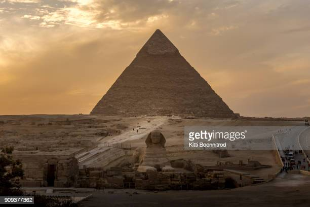 the great sphinx in front of pyramid of khafre during sunset in egypt - giza pyramids stock pictures, royalty-free photos & images