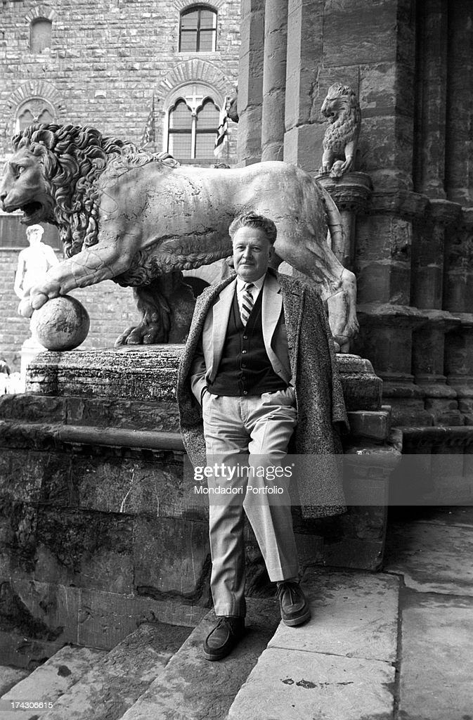 The great Turkish poet Nazim Hikmet smiles to the camera near the pedestal of Benvenuto Cellini's Perseus in the Loggia dei Lanzi; he's in Florence for the International Writers' Congress. Florence (Italy), March 1962..