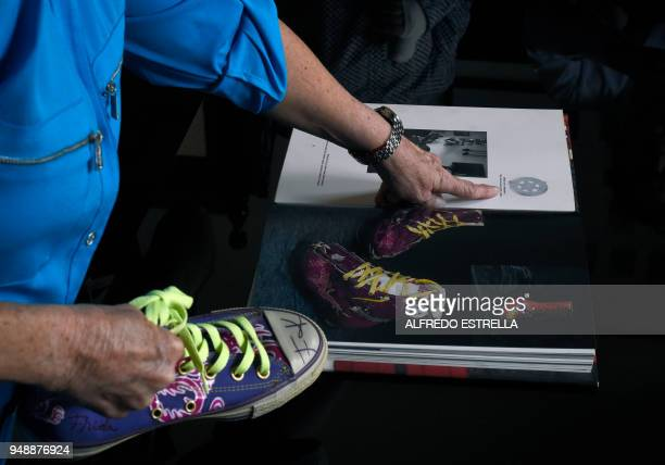 The greatniece of late Mexican artist Frida Kahlo Mara Romeo shows a book with a photo of Frida's shoes during an interview with AFP at a family...