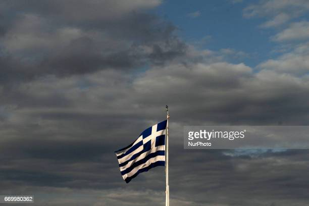The Greek flag atop the Acropolis Hill in Athens Greece on April 18 2017 Every year on 18 April ICOMOS International council on monuments and sites...