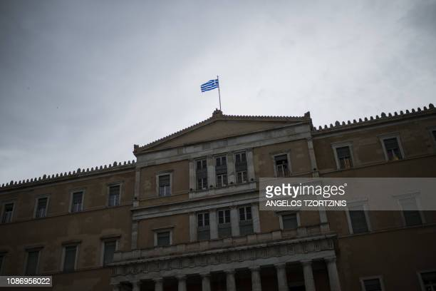 The Greek flag flutters above of the Greek Parliament building in Athens on January 23, 2019. - The Greek parliament began on January 23 to discuss...