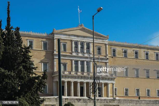 The Greek flag flutters above of the Greek Parliament building in Athens on January 24, 2019. The discussion and processing of the draft law...