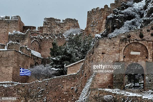 The Greek flag flutters over a snowcovered castle in Ancient Corinth some 80 km west of Athens on December 29 2016 Snowfall and strong winds have...