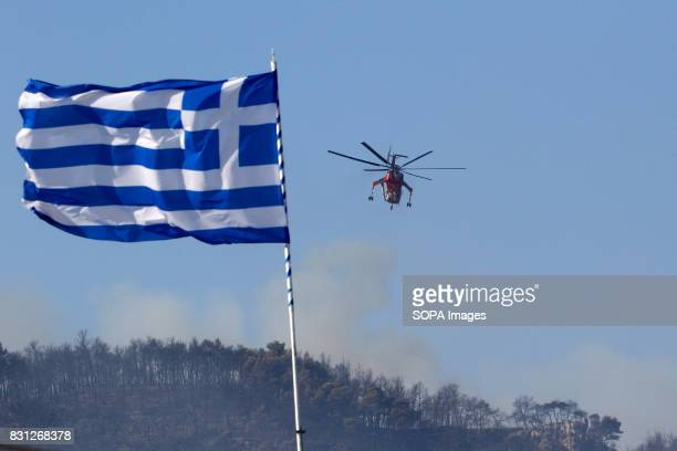 The Greek flag is seen while the fire helicopter thrown water on the forest fire
