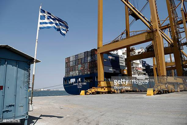 The Greek national flag flies on the dockside as shipping containers sit aboard cargo vessel Santa Bettina operated by Reederei ClausPeter Offen GmbH...