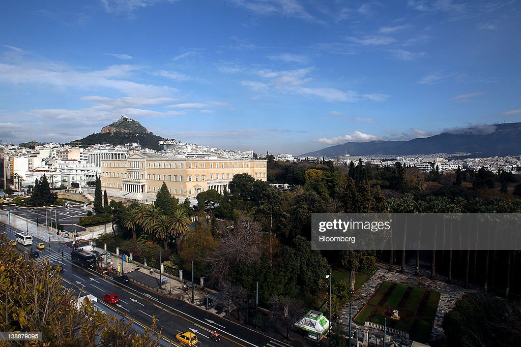 The Greek parliament building and Syntagma Square, left, are seen in Athens, Greece, on Sunday, Feb. 12, 2012. Greek Prime Minister Lucas Papademos won parliamentary approval for austerity measures to secure an international bailout after rioters protesting the measures battled police and set fire to buildings in downtown Athens. Photographer: Simon Dawson/Bloomberg via Getty Images