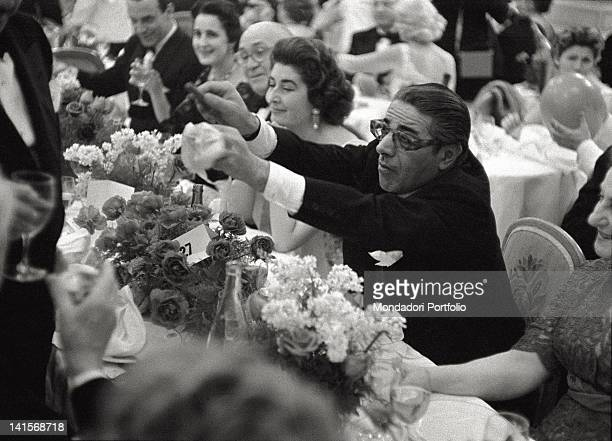 The Greek shipowner Aristotle Onassis makes to light a cigar to the waiter during an elegant dinner in a restaurant in Montecarlo by that time his...