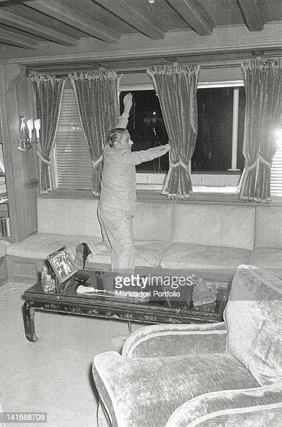 The greek shipowner Aristotle Onassis move courtains in one of the most beautiful rooms on board of his yacht 'Christina O' so called in honour of...