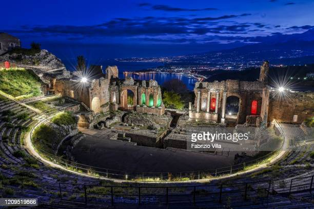 The Greek theatre in Taormina at sunset with no visitors following the restrictions imposed by the Government for the current Covid19 emergency In...