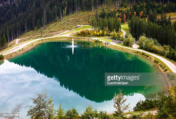 The green mountain lake Seidlalm See at Hahnenkamm slope which is used for the production of artificial snow in the tyrolean alps on October 05 2012...