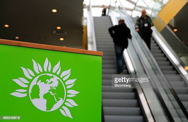 The Green Party logo sits on a sign as visitors travel on escalators during the party's spring conference in Liverpool UK on Friday March 6 2015...