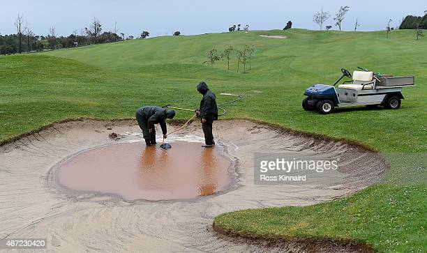 The greens staff pump water out of a bunker next to the 18th green prior to the second and final round of the Madeira Islands Open at the Santo da...