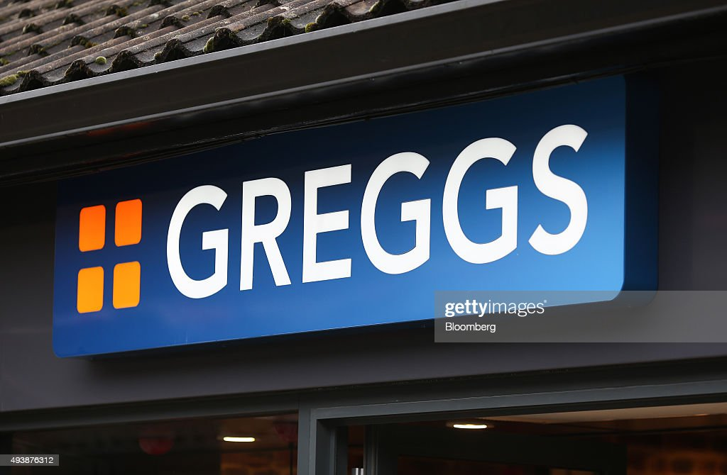 The Greggs logo sits on a sign above the entrance to a Greggs Plc sandwich chain outlet in Caterham, U.K., on Thursday, Oct. 22, 2015. Same-store sales at Greggs have grown 5.6 percent so far in 2015, up from 3.9 percent across the same period last year, and the company said on Oct. 6 that full-year growth will exceed its previous forecast slightly. Photographer: Chris Ratcliffe/Bloomberg via Getty Images