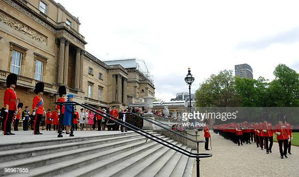 The Grenadier Guards march past Queen Elizabeth II after being presented with their new colours in the garden of Buckingham Palace on May 11 2010 in...