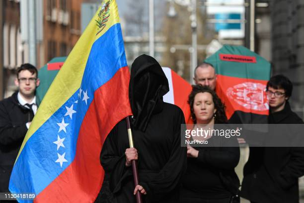 The Grim Reaper with Venezuelan flag leads a funeral cortege including coffins draped in the flags of Syria Afganistan and Libya and Eilis Ryan...
