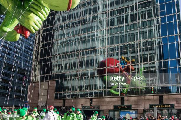 The Grinch balloon floats over Sixth Avenue during the 91st annual Macy's Thanksgiving Day Parade on November 23 2017 in New York City