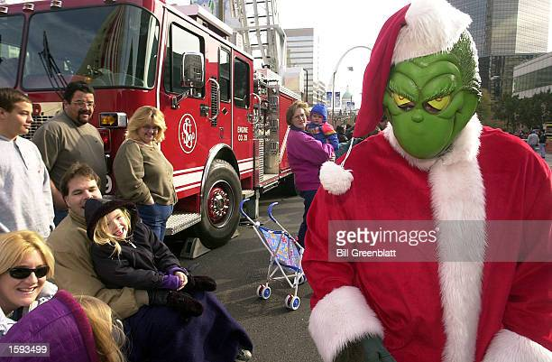 The Grinch that stole Christmas eyes the young children and parents as he makes his way up Market Street during the Thanksgiving Day Parade November...
