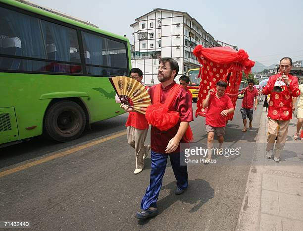 The groom Alan Gauthier from USA and his Chinese bride Li Ling in a sedan chair parade on a street during a wedding ceremony at Ciqikou ancient...