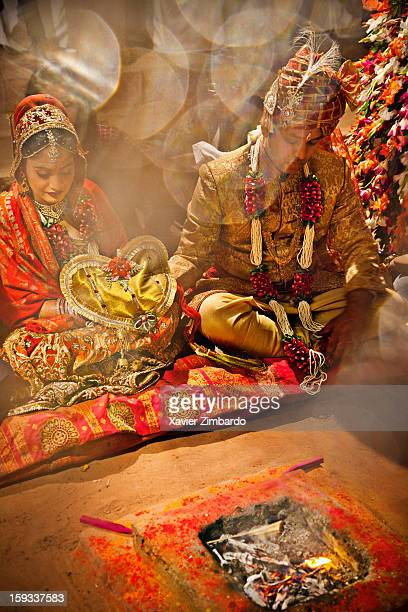 The groom and bride dressed up in traditional attire sitting together holding each other's hand in front the firedeity performing the wedding custom...