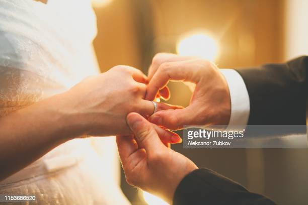the groom puts the ring on the bride's hand. hands of the newlyweds on the wedding day, close-up. the exchange of rings during the marriage. - fidanzato foto e immagini stock