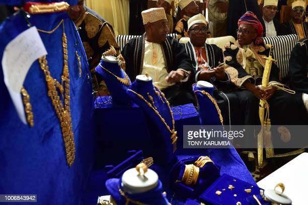 The groom waits with his offering of golden jewelry alongside some of his kin to be ushered to his bride at the bride's home during a traditional...