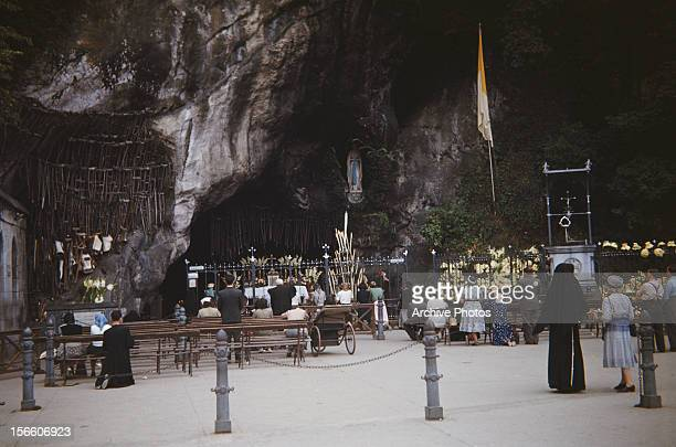 The Grotto in Lourdes southwest France circa 1960 The crutches on the left belonged to people who claimed to have been cured of their afflictions at...