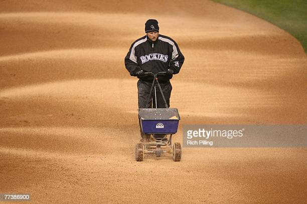 The ground crew spread diamond dust onto Coors Field during the National League Championship game between the Colorado Rocklies and Arizona...