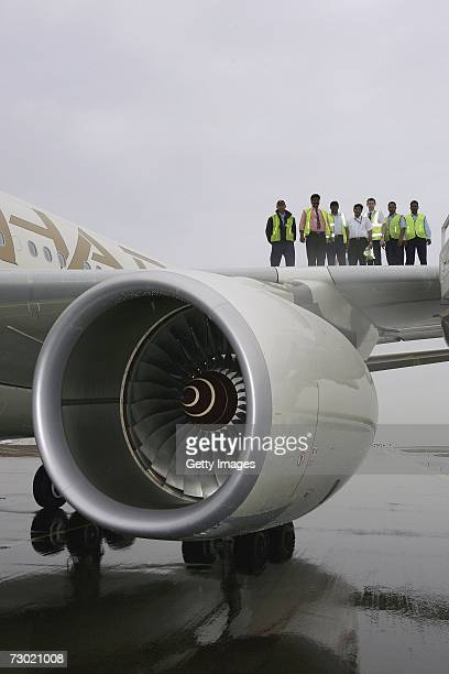 The ground crew stand on the wing of an Etihad Airways Airbus A340 parked on the runway at the Abu Dhabi International Airport during the 'Etihad...
