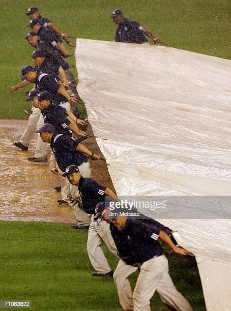 The grounds crew bring out the tarp during a ninthinning rain delay btween the New York Yankees and the Kansas City Royals at Yankee Stadium May 26...