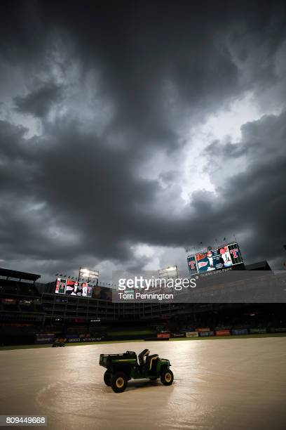 The grounds crew finishes covering the field during a rain delay prior to the Texas Rangers taking on the Boston Red Sox at Globe Life Park in...