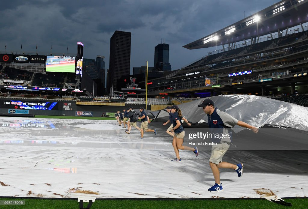 The grounds crew for Target Field pulls the tarp as rain delays the start of the game between the Minnesota Twins and the Tampa Bay Rays on July 12, 2018 in Minneapolis, Minnesota.