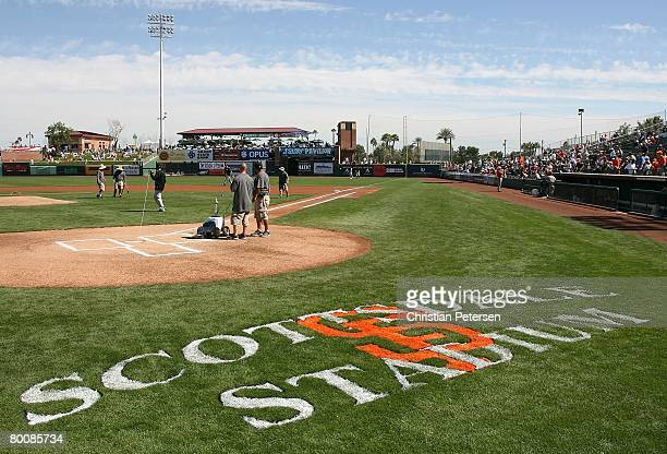 The grounds crew prepare the field at Scottsdale Stadium before the spring training game between the San Francisco Giants and the Oakland Athletics...