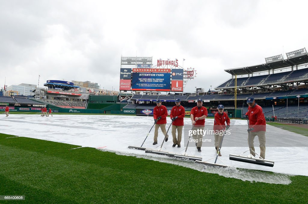 The grounds crew pushes water off the tarp before the game between the Washington Nationals and the Miami Marlins at Nationals Park on April 6, 2017 in Washington, DC.