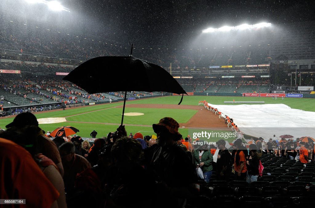 The grounds crew puts the tarp on the field at Oriole Park at Camden Yards in the 10th inning of the game between the Baltimore Orioles and the Toronto Blue Jays on May 19, 2017 in Baltimore, Maryland.