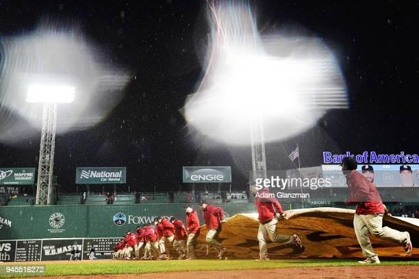 The grounds crew puts the tarp on the field at the top of the sixth inning due to a rain delay during a game between the Boston Red Sox and the New...