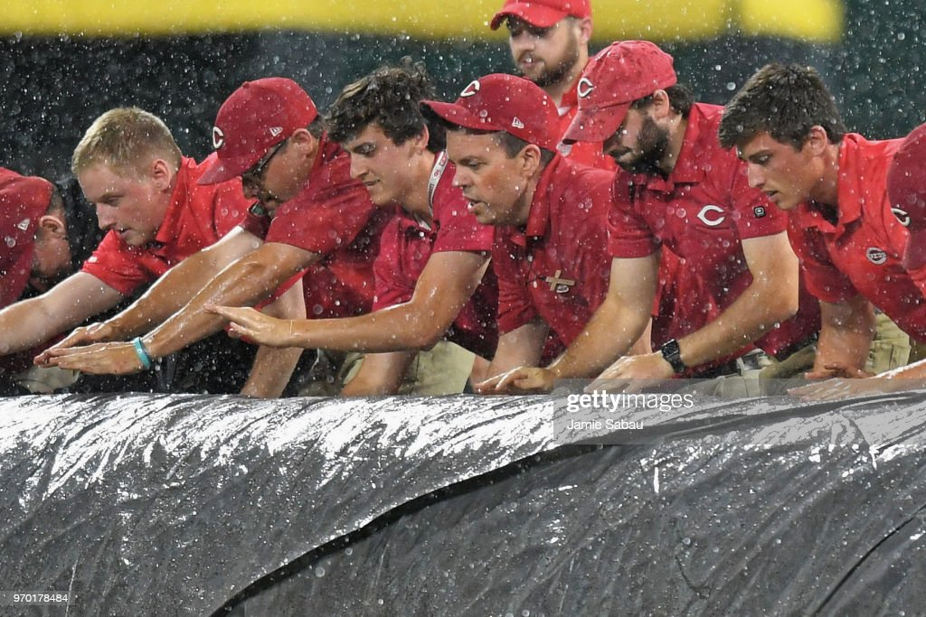 The grounds crew rolls out the tarp at the start of a rain delay in the bottom of the ninth inning at Great American Ball Park during a game between the Cincinnati Reds and the St. Louis Cardinals on June 8, 2018 in Cincinnati, Ohio.
