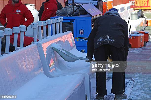 The grounds crew scrapes ice from the team benches on a subzero morning before an NFL game between two divisionleading teams the Tennessee Titans and...