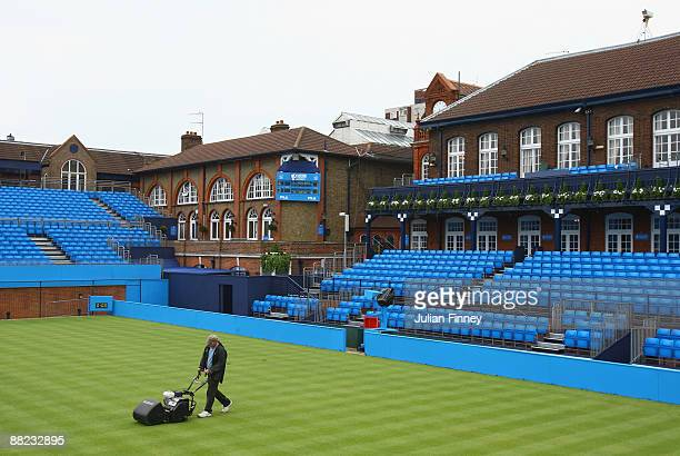 The groundsman cuts the grass on centre court as the new layout turns from red to blue at Queens Club on June 5, 2009 in London, England. The newly...