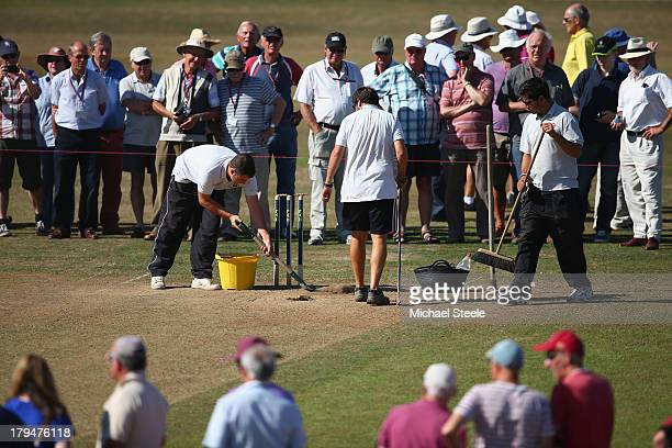 The groundsmen make running repairs to the wicket during the tea interval on day two of the LV County Championship Division One match between...